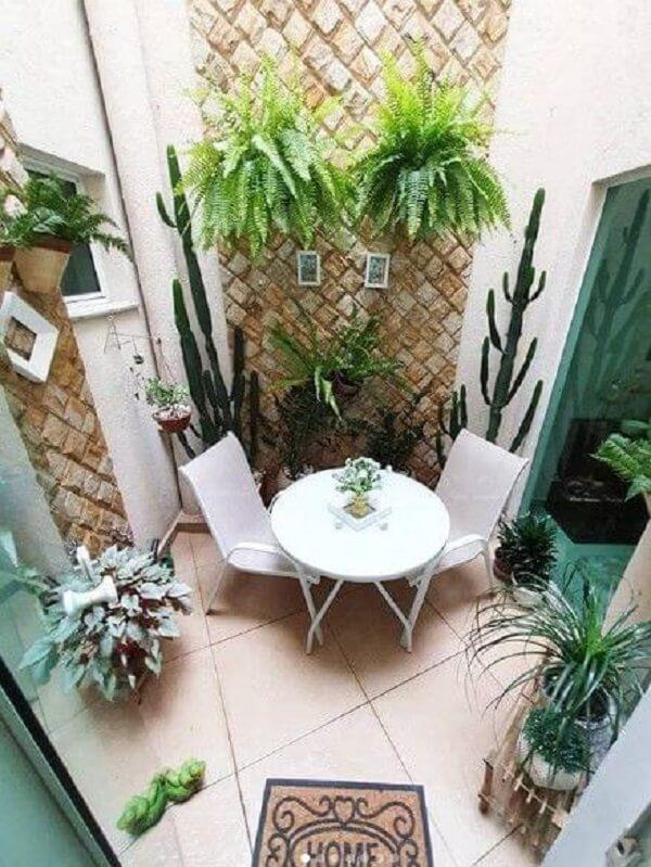 Jardim de inverno com mesa e cadeiras brancas