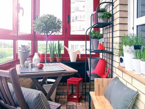 Mesa e cadeira de madeira, janela com moldura vermelha e vasos em um aparador preto