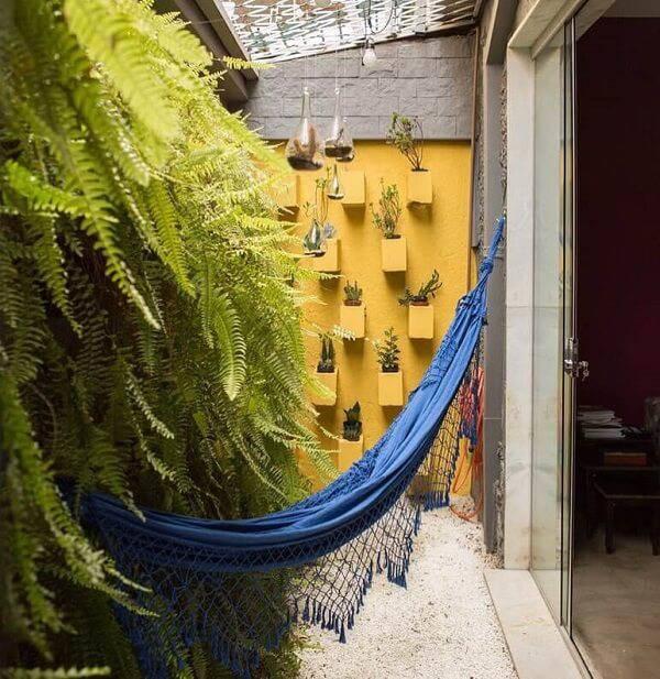 Samambaia, rede azul estendida, vasos suspensos em uma parede amarela