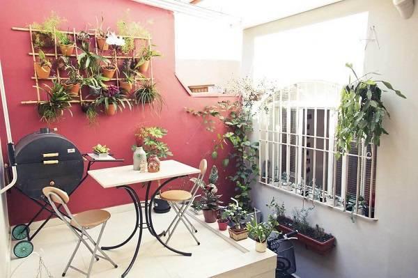 Parede vermelha com vasos suspensos, churrasqueira, mesa e duas cadeiras