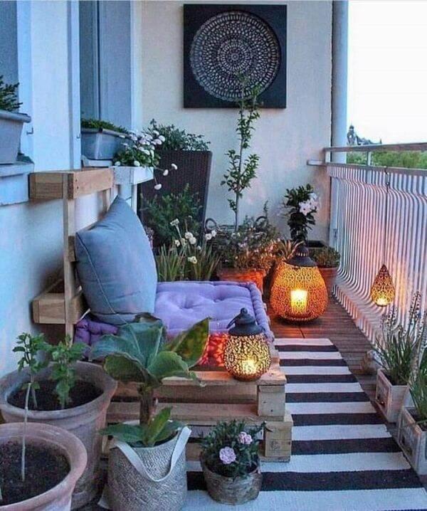Ambiente com diversos vasos e um banco feito de pallet com almofadas