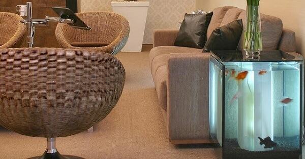 Posicione o aquário ao lado do sofá, pois sua estrutura pode ser usada como mesa lateral