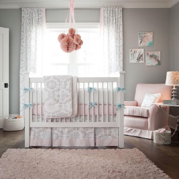 Quarto de bebê cinza e rosa com quadros decorativos e mobile de bolas