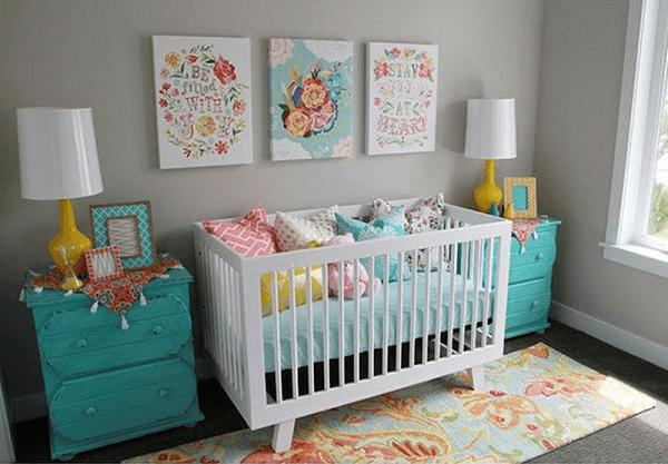 Quarto de bebê cinza com móveis azuis e almofadas coloridas