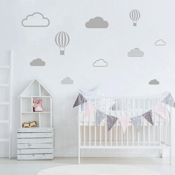 Quarto de bebê cinza com nuvens e balões e móveis brancos
