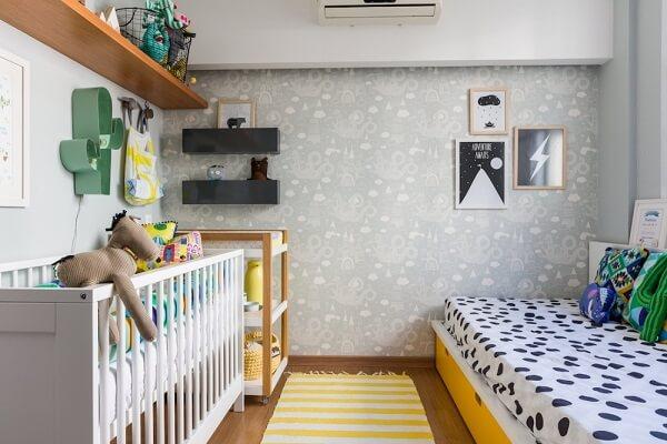 Quarto de bebê cinza com nuvens e papel de parede com desenhos diferentes