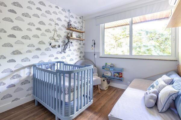 Quarto de bebê cinza com nuvens em papel de parede e berço azul
