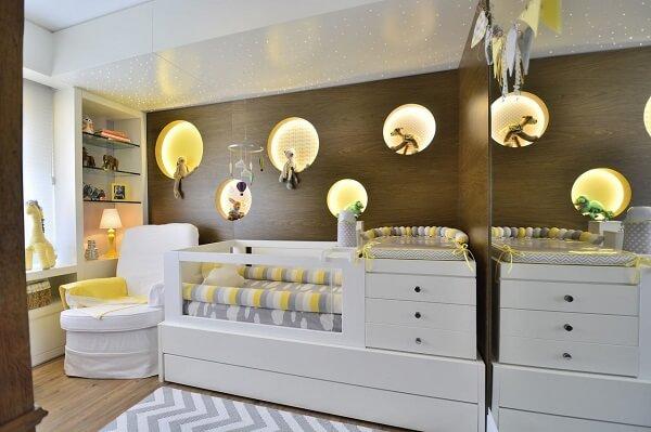 Quarto de bebê cinza e amarelo com móveis brancos planejados