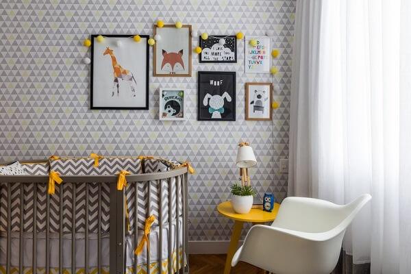 Quarto de bebê cinza e amarelo com mesa de centro amarela e parede estampada