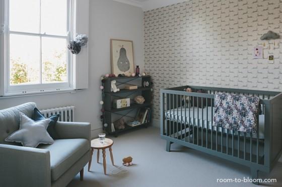 Quarto de bebê cinza e branco com estante e cômodas em tons mais escuros