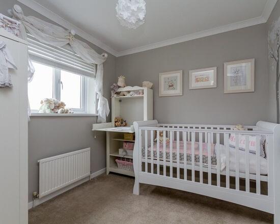 Quarto de bebê cinza e branco com móveis brancos