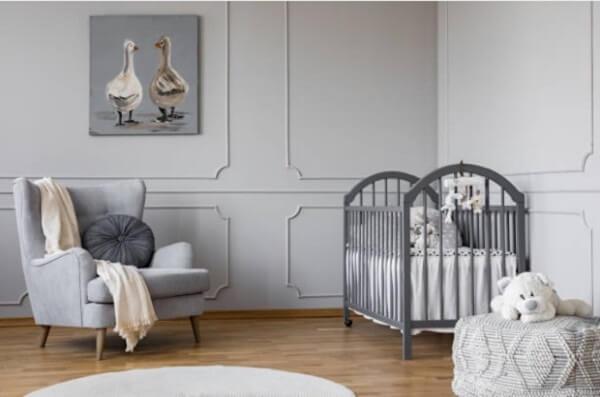 Quarto de bebê cinza e branco com poltrona e berço e quadro de pássaros