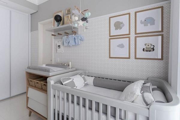Quarto de bebê cinza e branco com quadros na parede