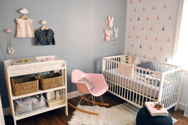 Quarto de bebê cinza e rosa com cabides suspensos e berço branco