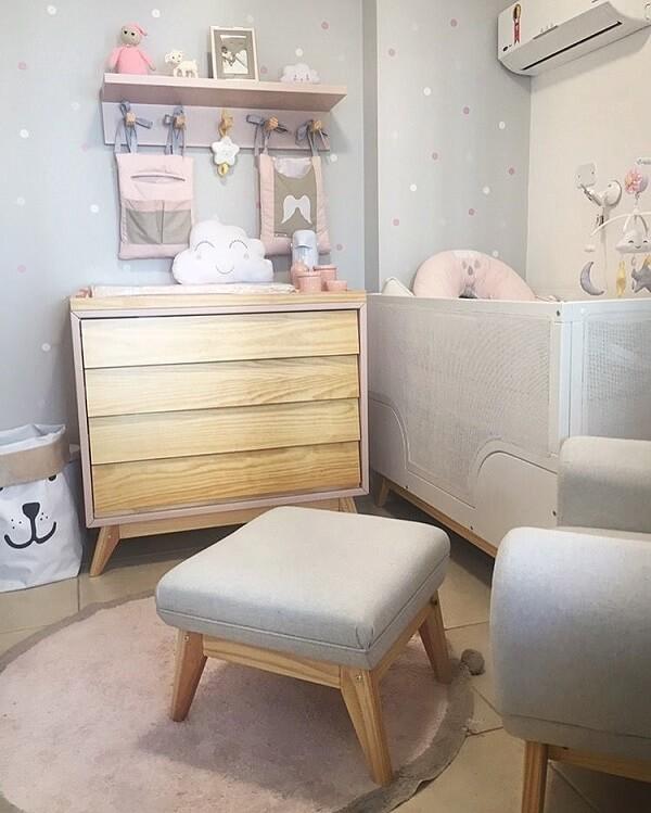 Quarto de bebê cinza e rosa com cômoda de madeira