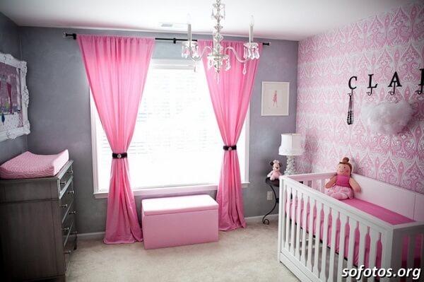 Quarto de bebê cinza e rosa com cortinas rosas e lustre