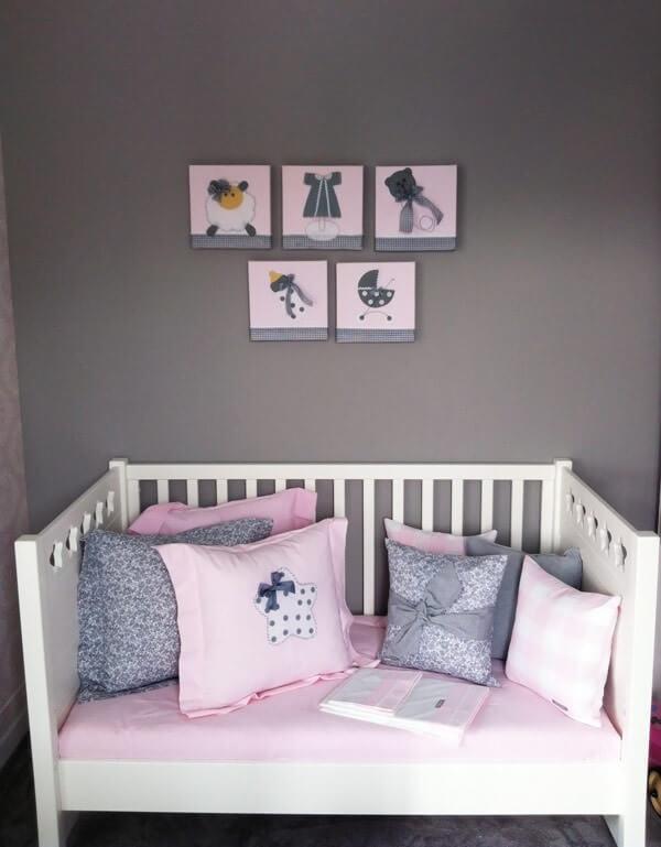 Quarto de bebê cinza e rosa com parede cinza escuro e quadros