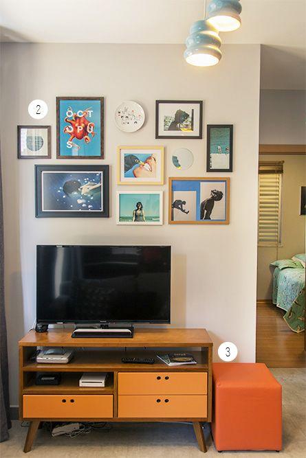 Sala de estar com rack retro de madeira com quadros coloridos