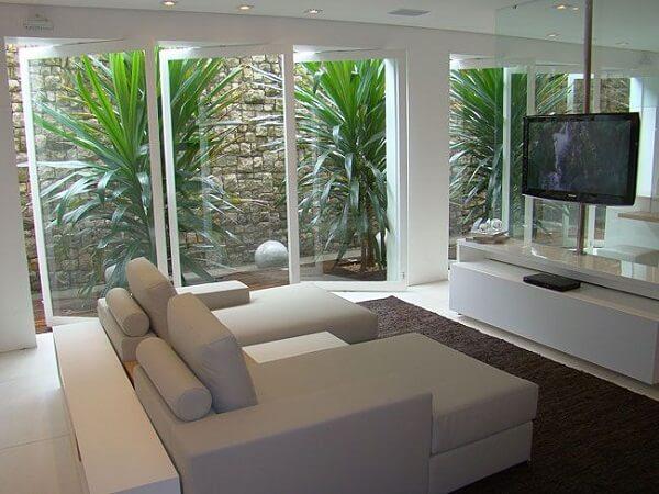 Sala de tv moderna com couro branco e portas de vidro