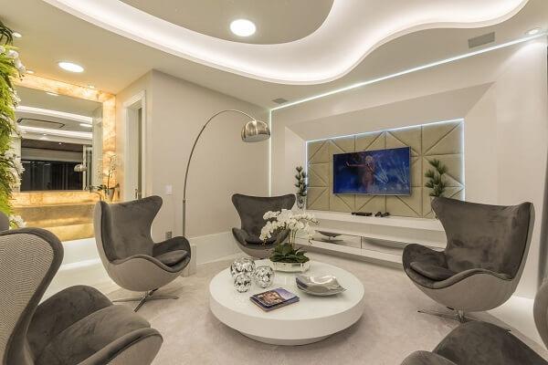 Sala de tv moderna com painel iluminado e poltronas marrons