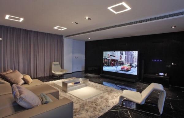 Sala de tv moderna decorada com parede preta e tapete felpudo