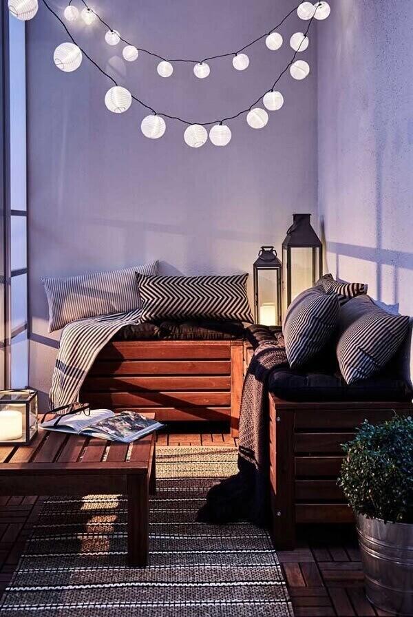 Varanda confortável com banco feito de pallet e lanternas marroquinas