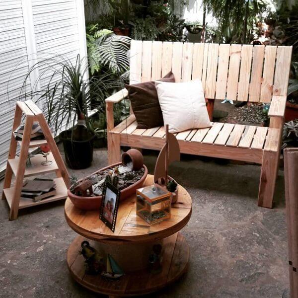 Varanda rústica com mesa de carretel e banco de pallet