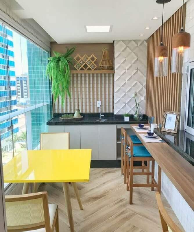 apartamento com área gourmet pequena e simples decorada com mesa amarela e cadeira azul Foto Dicas de Mulher