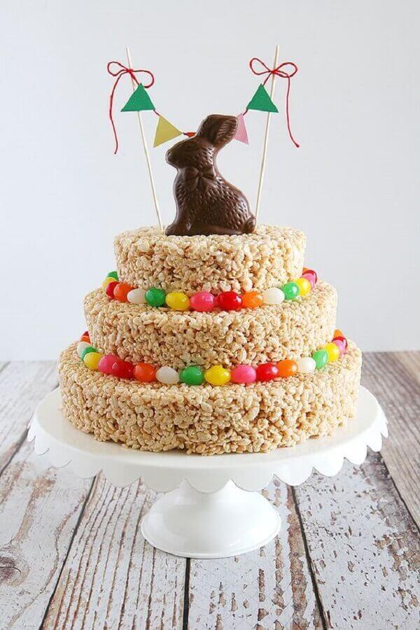 bolo de páscoa 3 andares decorado com coelho de chocolate e balinhas coloridas Foto Pinterest