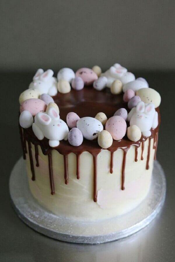 bolo de páscoa decorado com calda de chocolate e mini ovos coloridos Foto Deavita