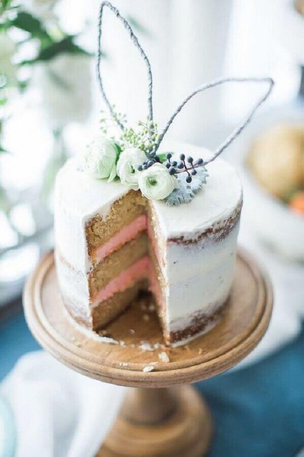 bolo de páscoa rústico decorado com orelha de coelho e flores no topo Foto Woman's Day