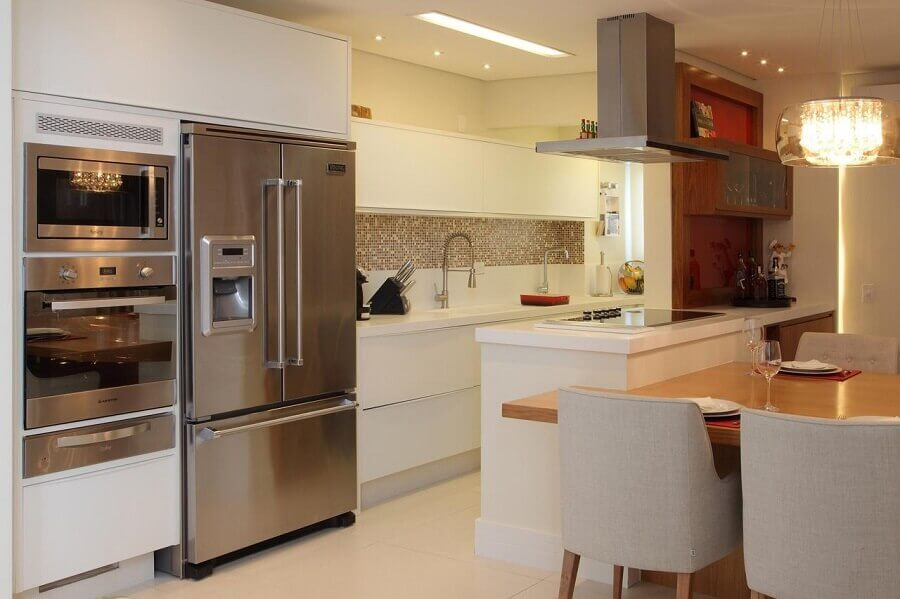 cozinha americana planejada com mesa de madeira integrada a bancada Foto Cris Paola