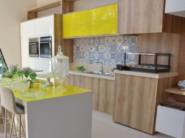 Cozinha com churrasqueira e decoração amarela na varanda alegre