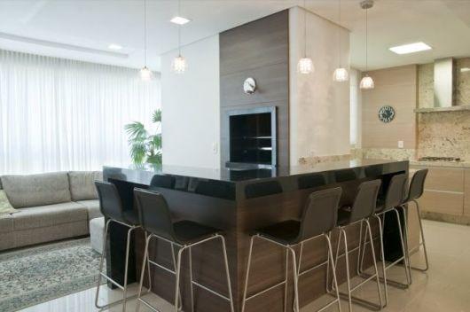 Cozinha com churrasqueira com bancos pretos