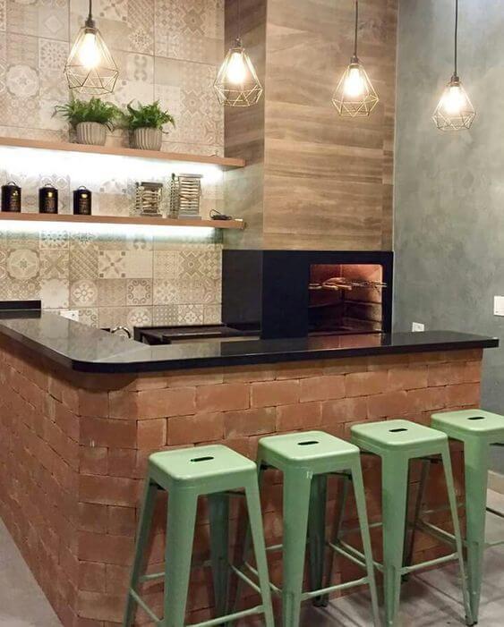 Cozinha com churrasqueira e banquetas para deixar o ambiente mais agradável para os convidados