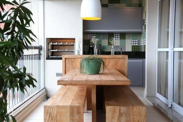 Mesa de madeira na cozinha externa com churrasqueira