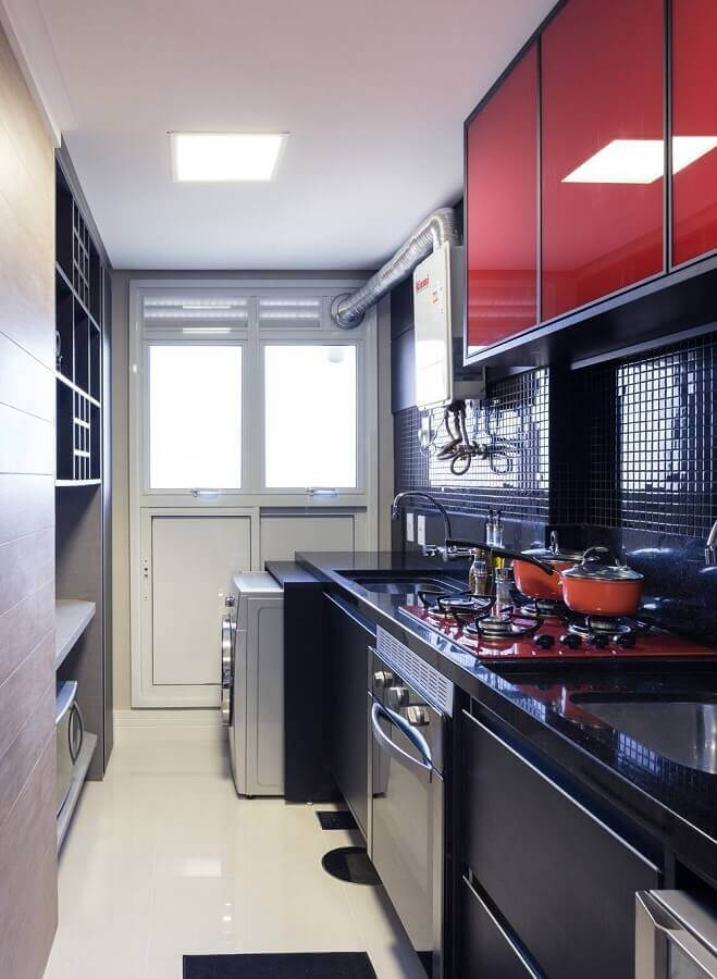 kitchen with small laundry room decorated with cabinets designed in red and black Foto Casa de Valentina
