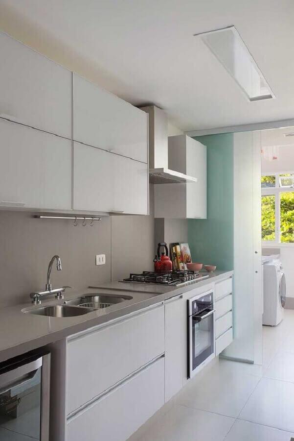 cozinha de apartamento pequeno com lavanderia separada por porta de vidro de correr Foto Casa de Valentina