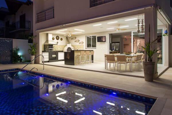 Cozinha externa com churrasqueira na área da piscina