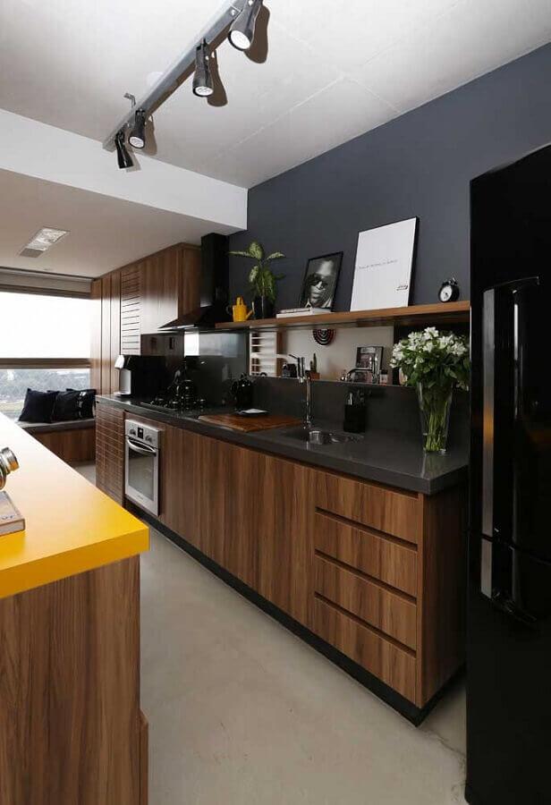 cozinha planejada com armários de madeira e paredes pintadas de preto Foto Archdaily