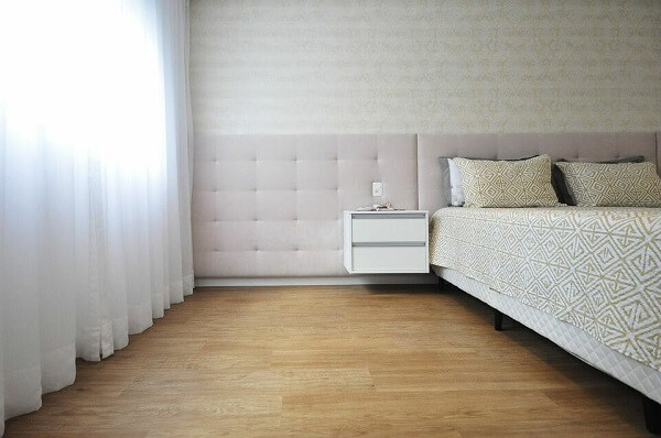 Cabeceira estofada e criado branco para a decoração do quarto