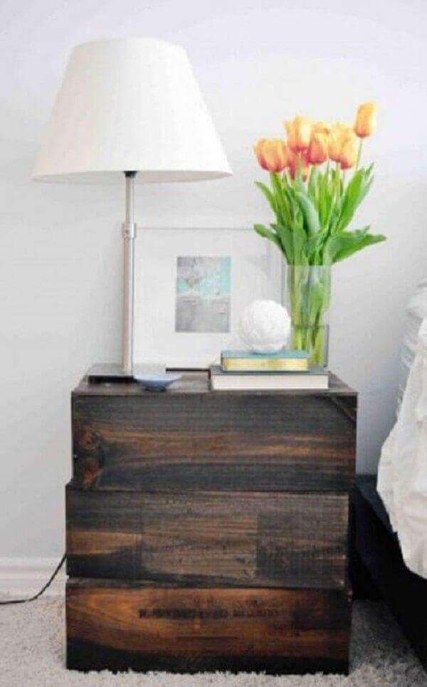 O criado mudo madeira escura complementa a decoração do quarto