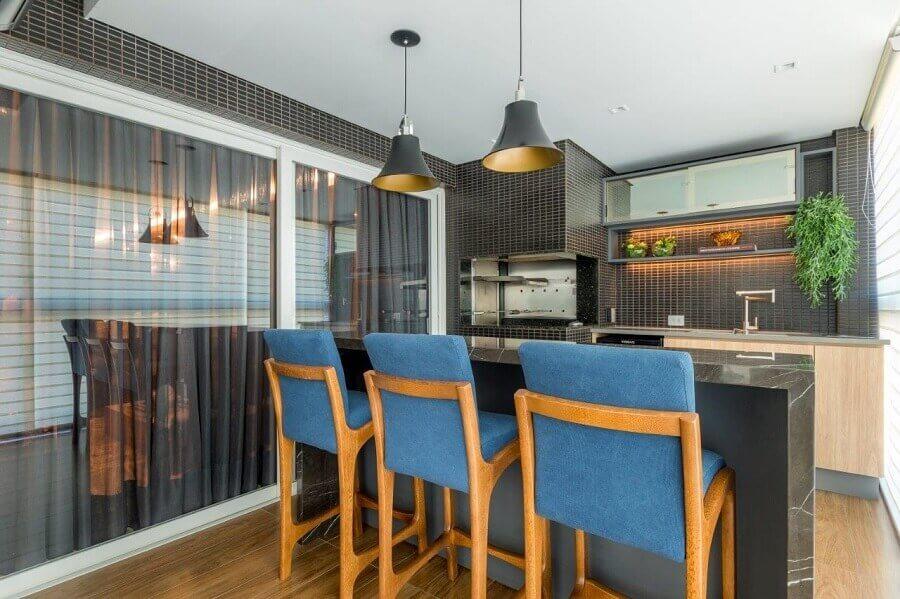 decoração com banquetas azuis e revestimento preto para área gourmet pequena com churrasqueira Foto Cristina Reinert