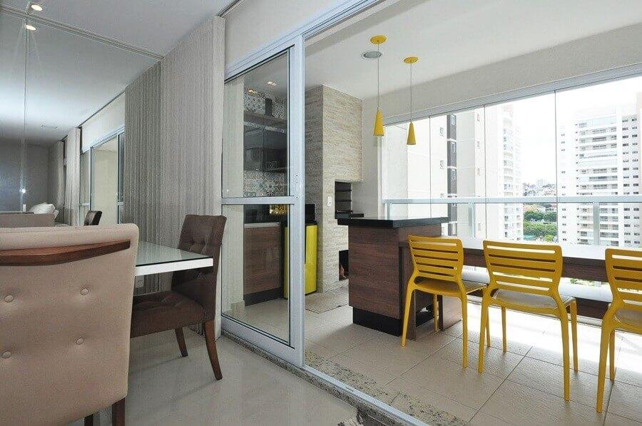 decoração com cadeiras amarelas para área gourmet pequena com churrasqueira Foto Condecorar Arquitetura e Interiores