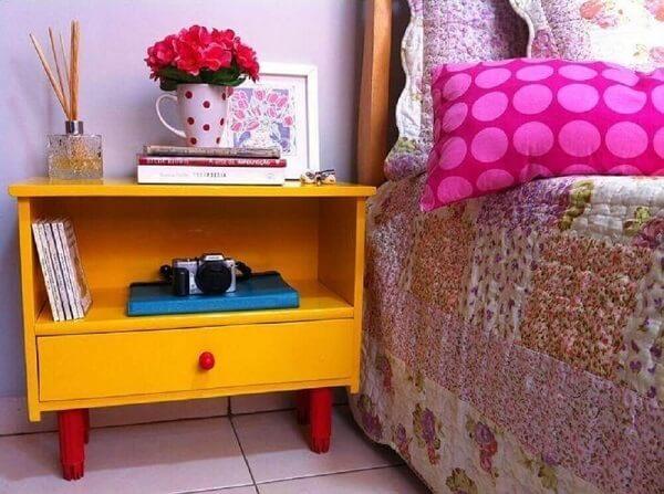O criado mudo amarelo traz alegria para a decoração do quarto
