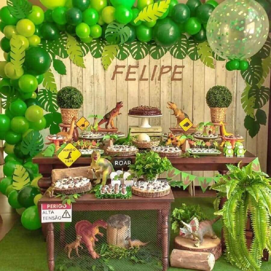 Dinosaur party decoration with wood panel decorated with foliage and green balloons Photo Andressa Oliveira