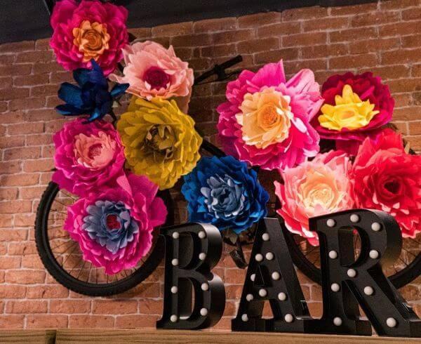 Decoração com flores de papel de seda gigantes e coloridas