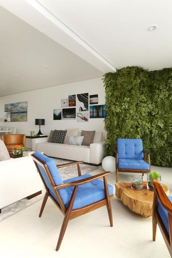 Sala de estar com jardim vertical e poltronas azuis