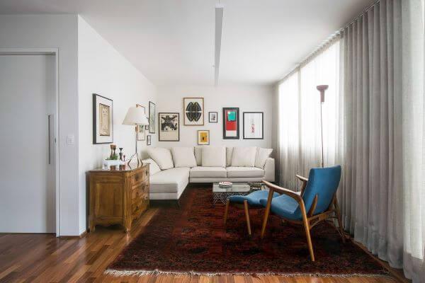 Sala de estar branca com poltrona de veludo azul