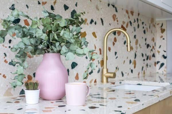 Revestimento de cozinha granilite com torneira dourada